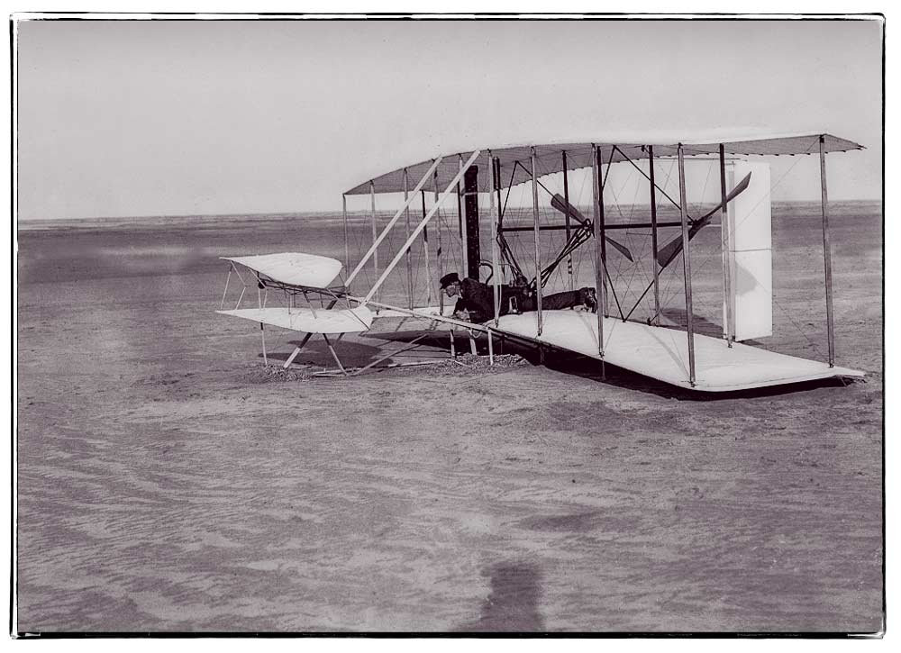 Wilbur in prone position in damaged machine on ground after unsuccessful trial of December 14, 1903; Kill Devil Hills, North Carolina