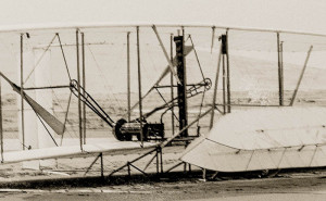 Dec 17, 1903-- Close-up view of damaged 1903 machine, rudder frame broken in landing, on ground at end of last flight