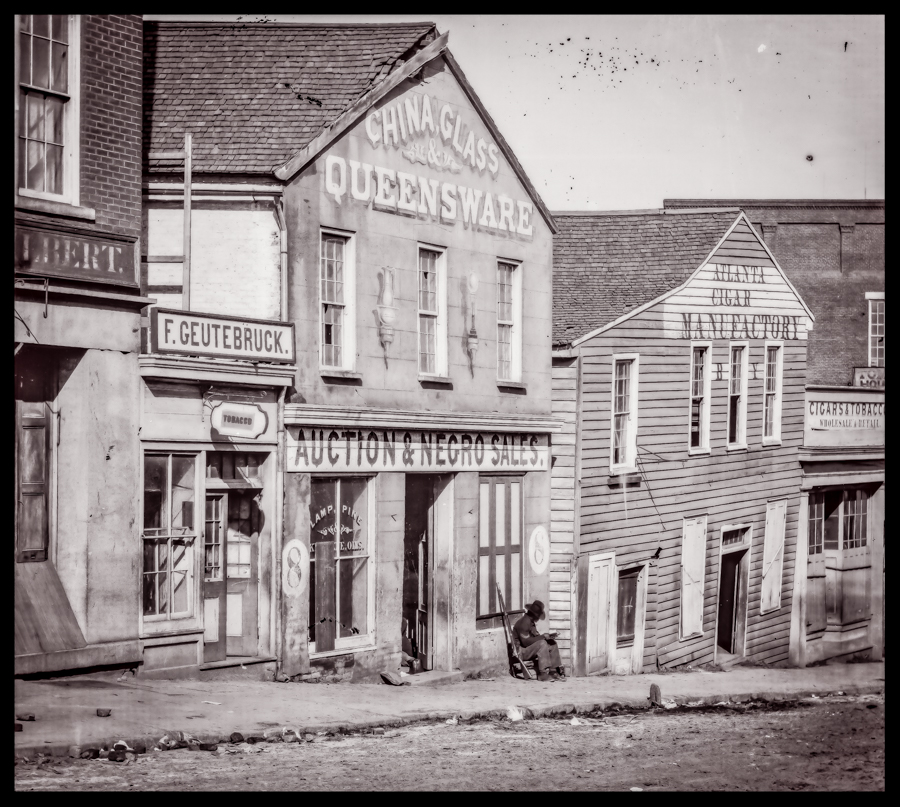 """This photo was taken by Barnard on Whitehall Street just a little south of the main railroad depot in downtown Atlanta. It shows a black corporal sitting outside of an auction house where """"negro"""" sales took place. I believe the photograph was staged and the Barnard took some delight in posing the black soldier reading a book outside of the auction house. Not many days after this image was taken, the area was burned."""
